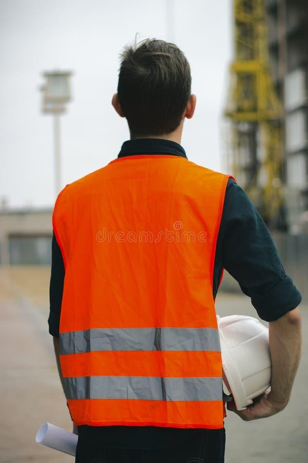 Arbeitskraft oder Bauvorarbeiter, der weißen Sturzhelm der Sicherheit halten und Plan, der in der Baustelle steht stockbilder