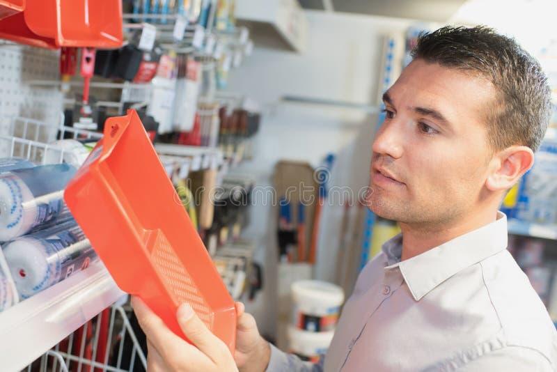Arbeitskraft oder Kunde, die Farbwanne am Baumarkt überprüfen stockbilder