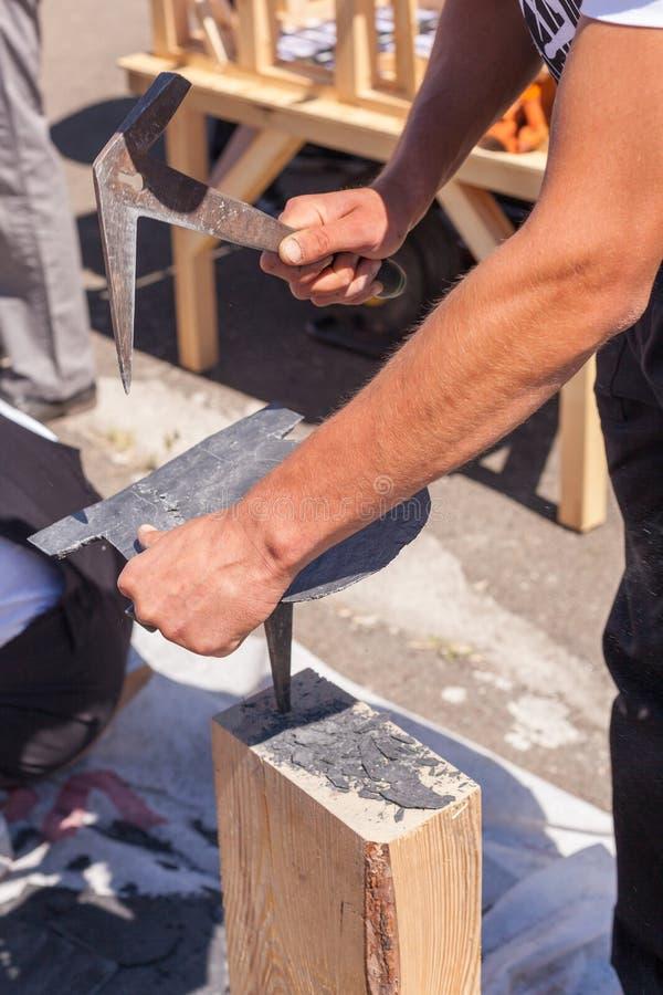 Arbeitskraft produziert Deckungsschiefer unter Verwendung eines Schieferhammers stockfoto