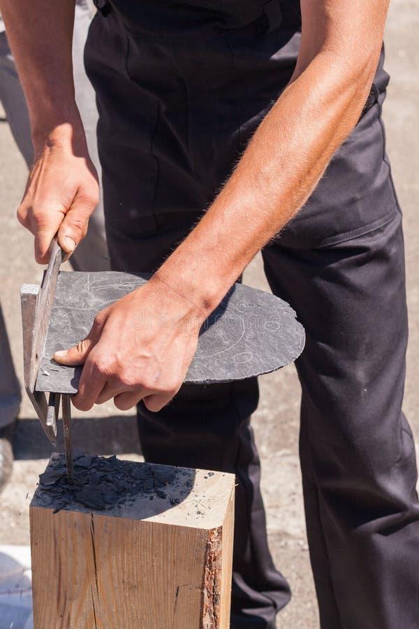 Arbeitskraft produziert Deckungsschiefer unter Verwendung eines Schieferhammers stockfotos