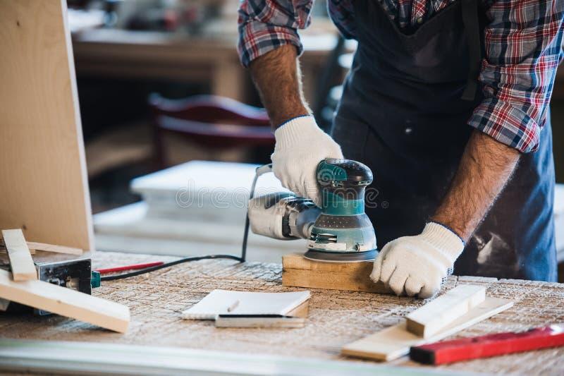 Arbeitskraft reibt das Holz der eckigen Schleifmaschine stockfoto