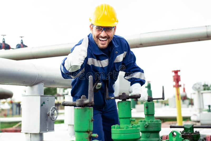 Arbeitskraft schließt das Ventil auf der Ölpipeline lizenzfreie stockfotografie