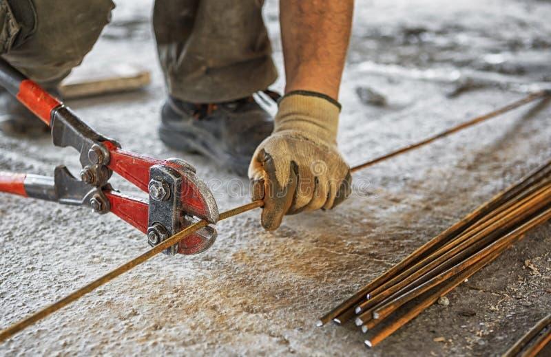 Arbeitskraft schneidet Stahlstangen mit Bolzenschneider stockfotos