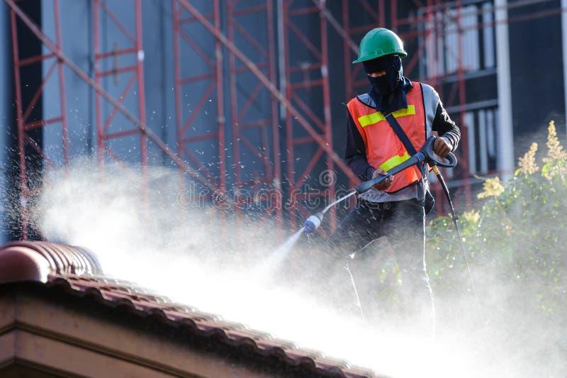Arbeitskraft in Sicherheitswesten-Reinigungsdachplatten mit Hochdruckreinigungsmaschine lizenzfreie stockfotos