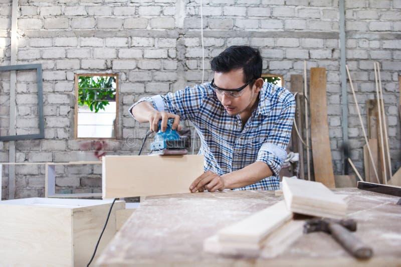 Arbeitskraft am Tischlerarbeitsplatz, der die Oberfläche des hölzernen Brettes weiter entwickelt lizenzfreies stockfoto