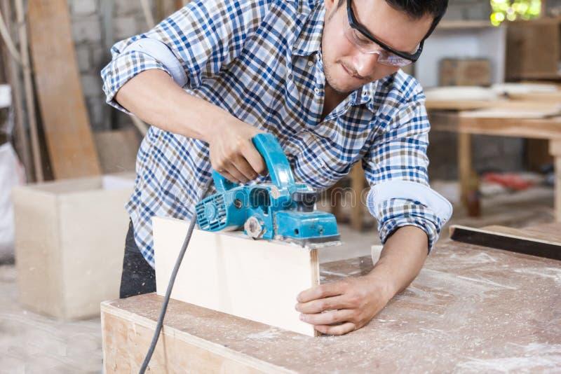 Arbeitskraft am Tischlerarbeitsplatz, der die Oberfläche von Möbeln u schneidet stockfoto
