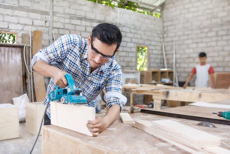 Arbeitskraft am Tischlerarbeitsplatz, der die Oberfläche von Möbeln u schneidet stockbilder
