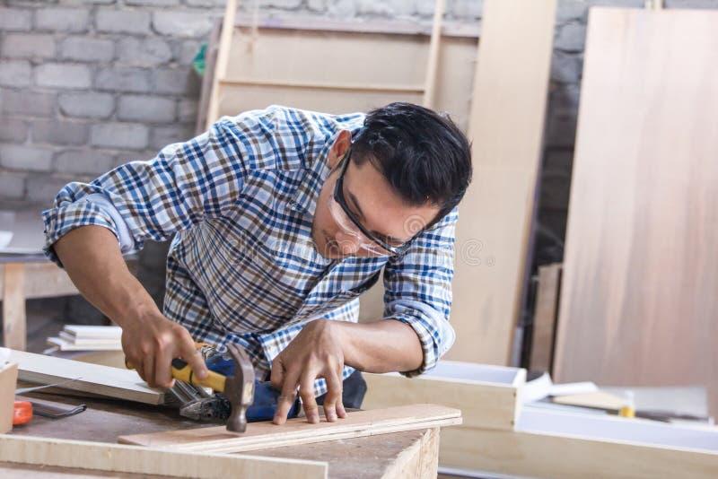 Arbeitskraft am Tischlerarbeitsplatz, der Nagel unter Verwendung des Hammers installiert stockfotografie