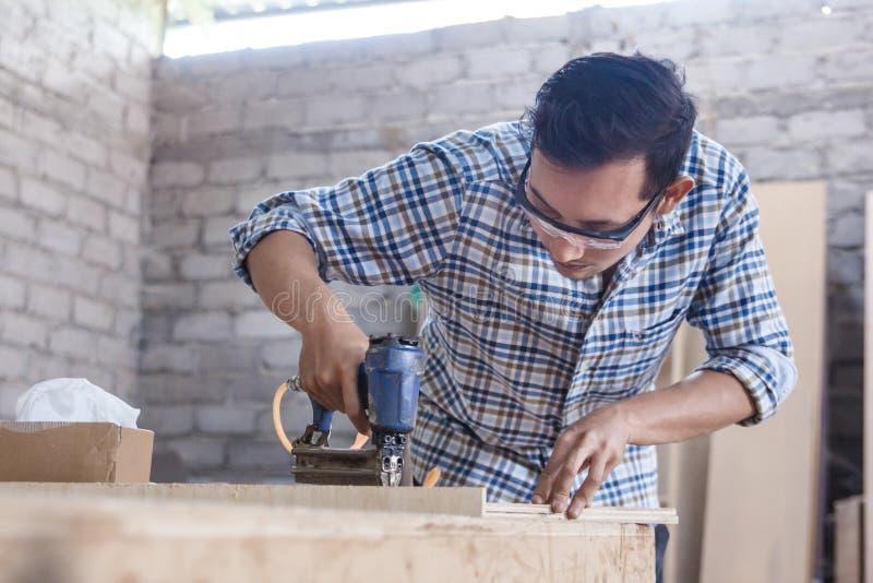 Arbeitskraft am Tischlerarbeitsplatz, der Nagel unter Verwendung pneumatischen Na installiert stockbilder