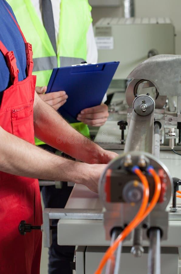 Arbeitskraft und Aufsichtskraft nahe bei Maschine stockbilder