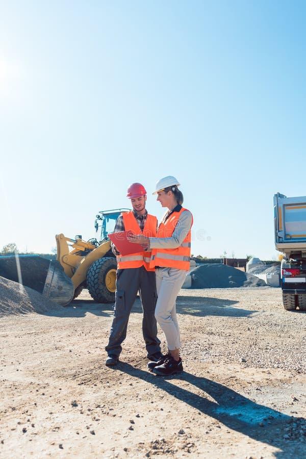 Arbeitskraft und Ingenieur auf BodenbewegungsBaustelleplanung lizenzfreies stockfoto