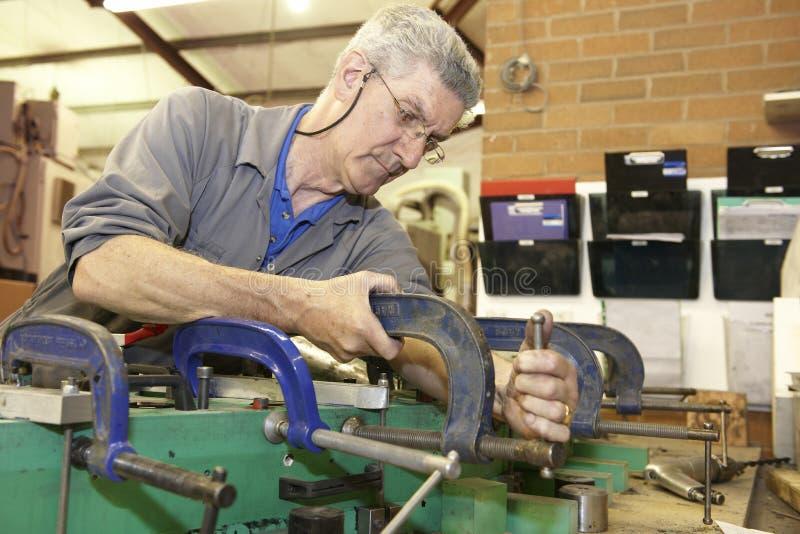 Arbeitskraft und Rohrschellen stockbilder