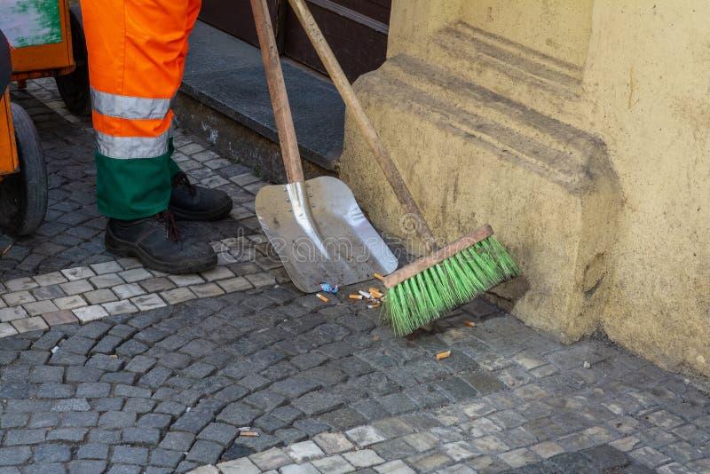 Arbeitskraft und Traktor Ein Hausmeister fegt Zigarettenkippen in der Straße lizenzfreie stockbilder