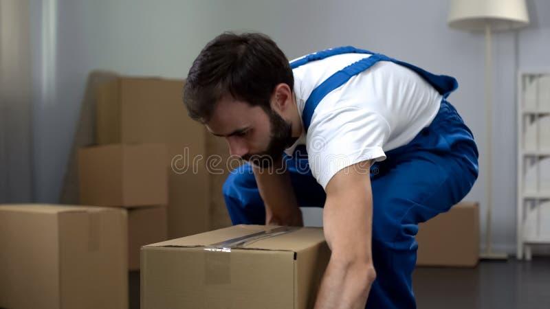 Arbeitskraft von tragender Pappschachtel des Umzugsunternehmens, Qualitätsverlegungsdienstleistungen stockfoto