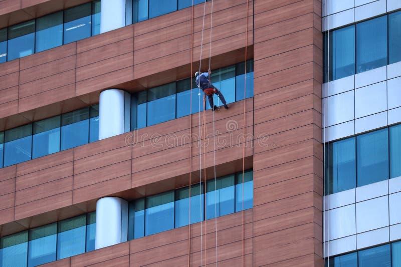 Arbeitskraft, welche die Glasfassade säubert stockfotos