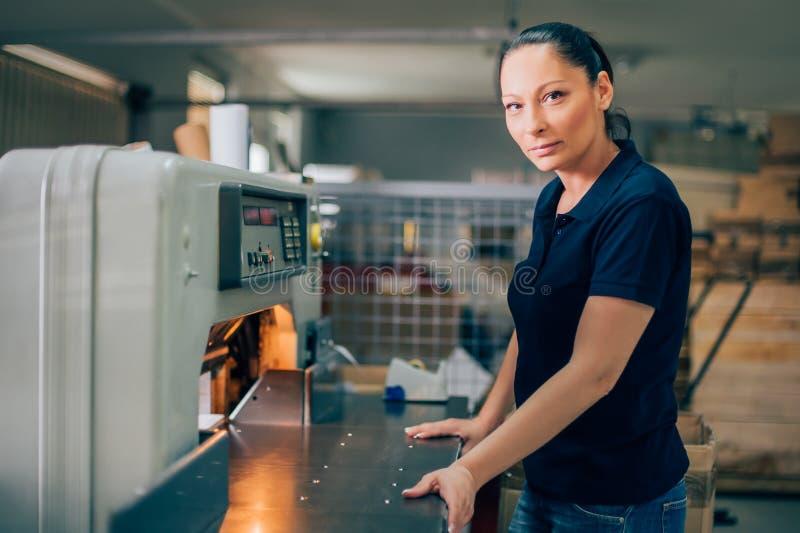 Arbeitskraft, wenn guillotinen-Maschinenmesser des centar Gebrauches Papiergedruckt wird lizenzfreie stockfotografie