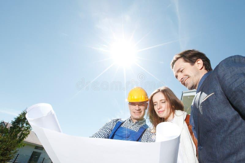 Arbeitskraft zeigt Hausausführungspläne lizenzfreie stockbilder