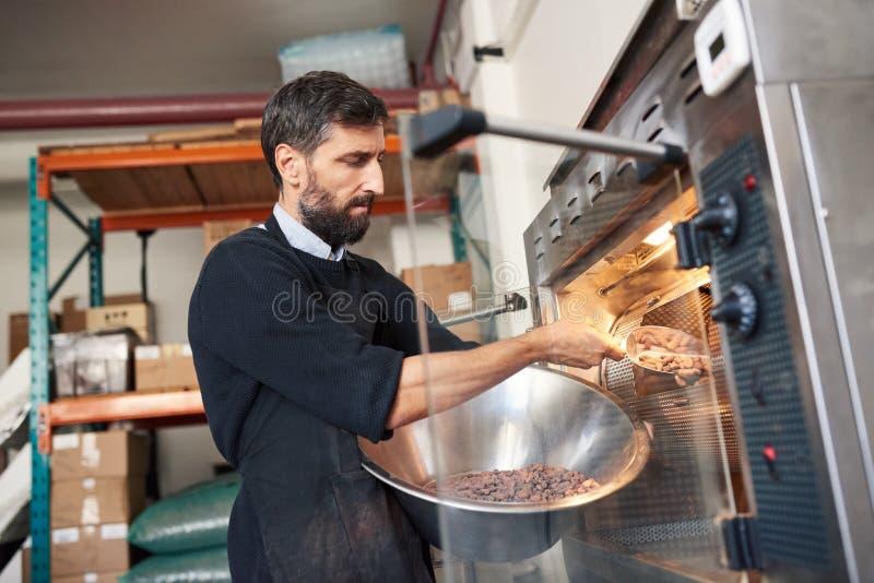 Arbeitskraftbratkakaobohnen in einer Schokoladenerzeugungsfabrik lizenzfreie stockfotos