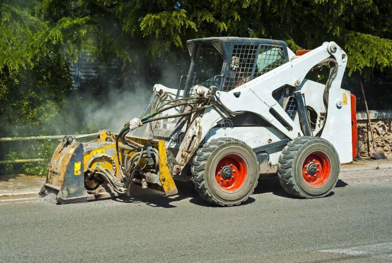 Arbeitskraftfahrer Skid-Ochse entfernen abgenutzten Asphalt stockfotos