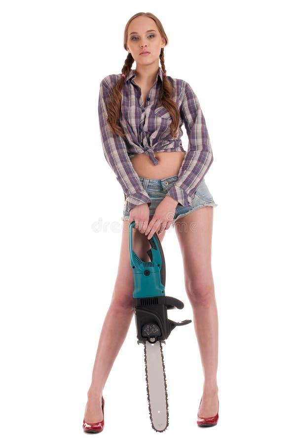 Arbeitskraftfrau im Jeansoverall mit Kettensäge lizenzfreie stockbilder