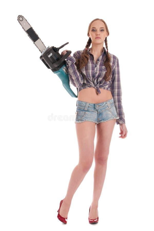 Arbeitskraftfrau im Jeansoverall mit Kettensäge stockbilder