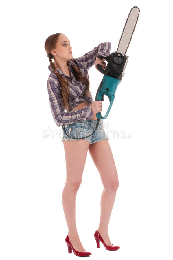 Arbeitskraftfrau im Jeansoverall mit Kettensäge lizenzfreie stockfotos