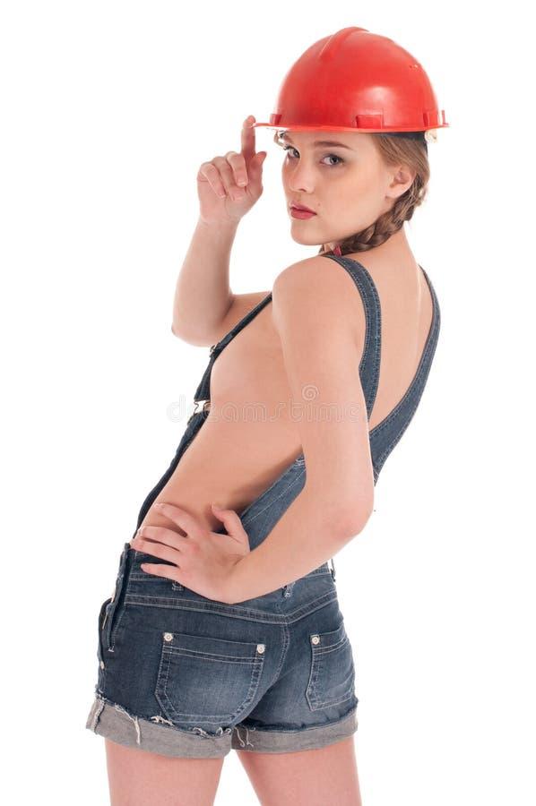 Arbeitskraftfrau im Jeansoverall und im orange Sturzhelm lizenzfreie stockfotos
