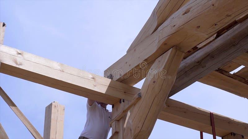 Arbeitskraftgestalt und Stapelbrettholzhaus clip Arbeitskräfte installieren schöne Holzbalken auf Baustelle des Hauses stockbild