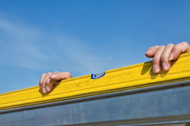Arbeitskrafthände beim Messen mit Geistniveau lizenzfreie stockfotos