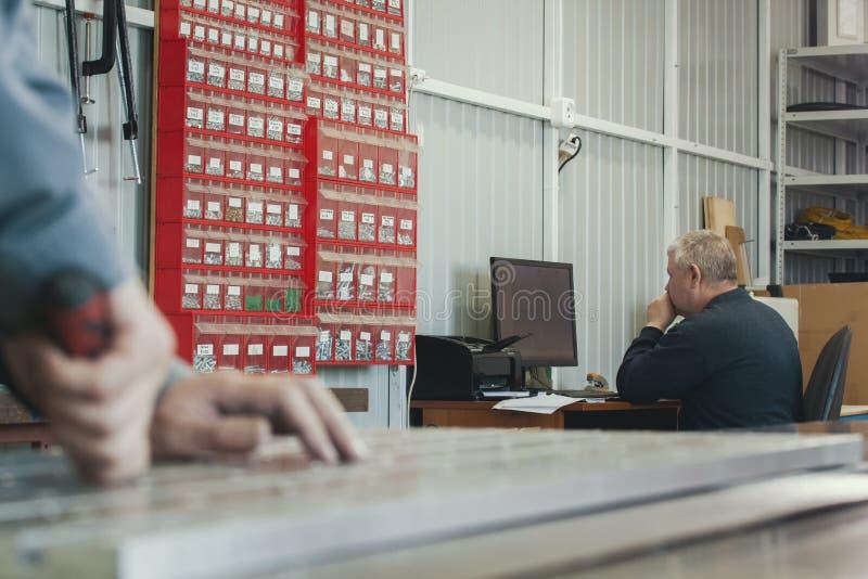 Arbeitskrafthände schnitten Metalldetail vor dem erwachsenen Mann, der am Computer an der Fabrik von Produktion CNC-Maschinerie a lizenzfreies stockbild