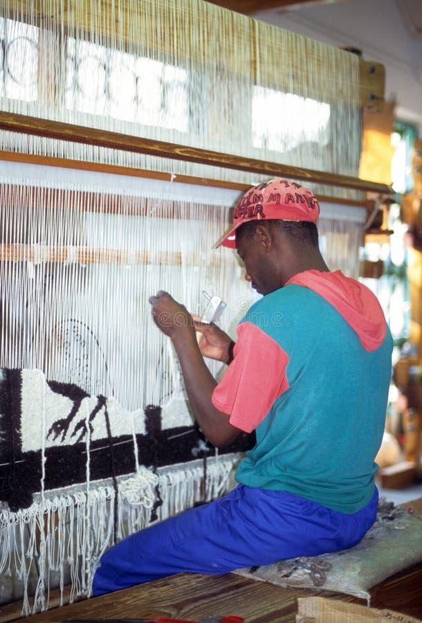 Arbeitskrafthand, die einen Wolleteppich spinnt lizenzfreie stockfotos