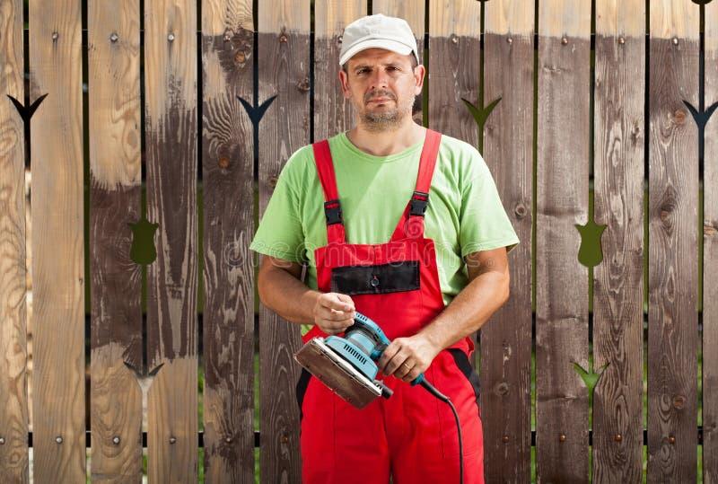 Arbeitskraftmann, der alte Farbe vom Zaun mit elektrischem Handwerkzeug reibt lizenzfreies stockbild