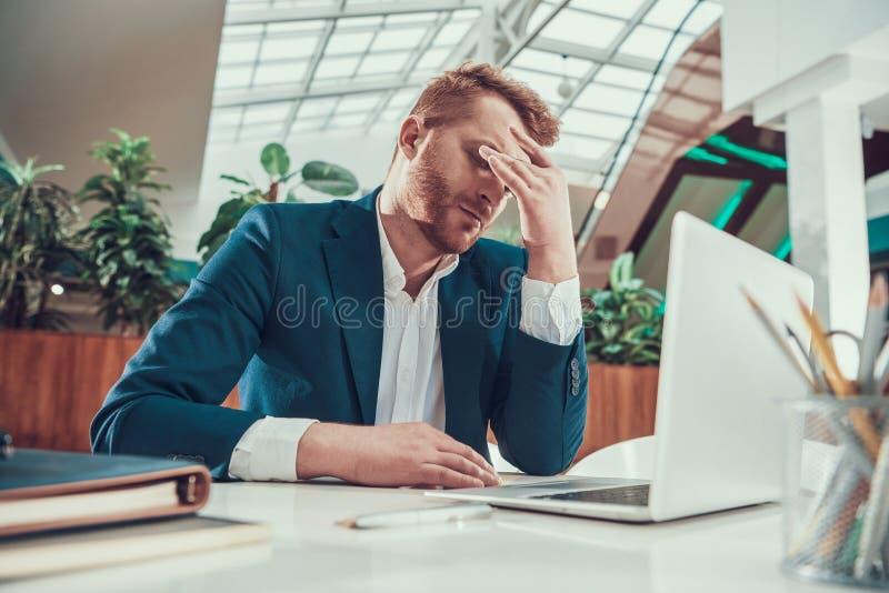 Arbeitskraftmann ist am Schreibtisch im Büro müde stockbild