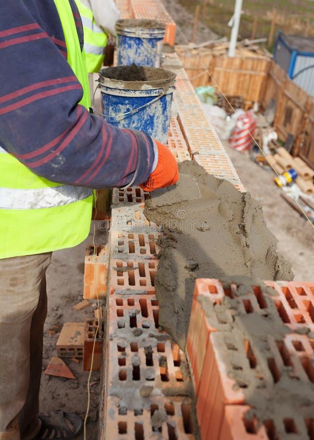 Arbeitskraftmauerziegelwände an der HausBaustelle, am Maurer und am Zement stockbild