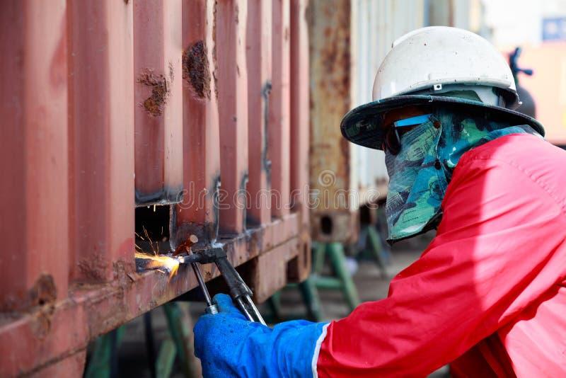 Arbeitskraftreparatur-Behälterkasten durch Brennschneiden und Schweißen, Job, wor stockfotos