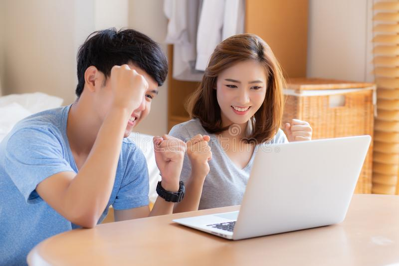 Arbeitslaptop der schönen Paare des Porträts jungen asiatischen mit Lächeln und glücklichem Sitzen im Schlafzimmer, im Mann und i lizenzfreies stockbild