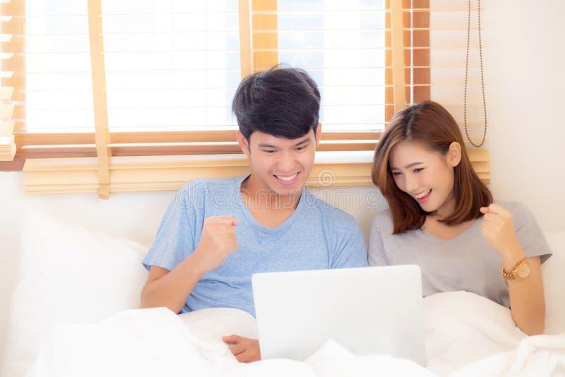 Arbeitslaptop der schönen Paare des Porträts jungen asiatischen mit Lächeln und glücklichem Sitzen im Schlafzimmer, im Mann und i lizenzfreie stockfotografie