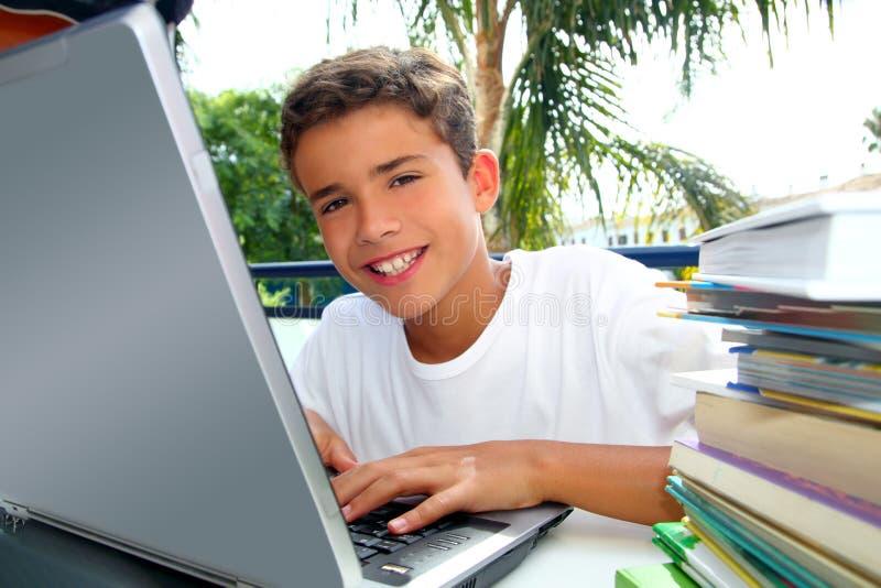 Arbeitslaptop des glücklichen Jugendlichkursteilnehmer-Jungen stockfotos