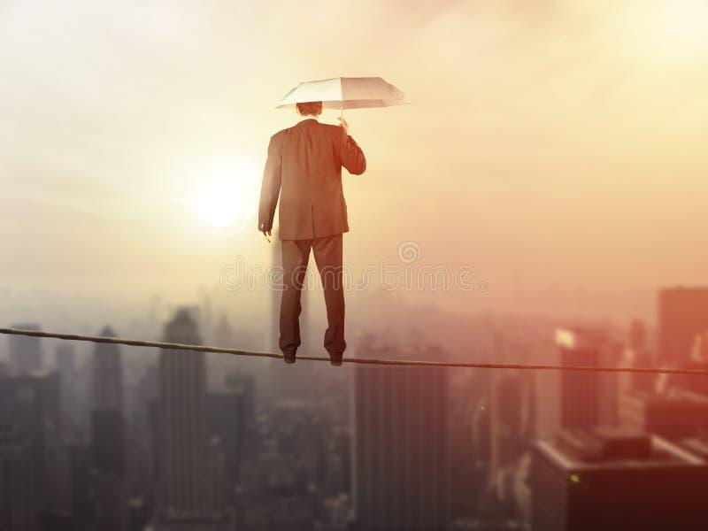 Arbeitsleben-Balancenkonzept: Geschäftsmann, der über der Stadt balanciert stockbild