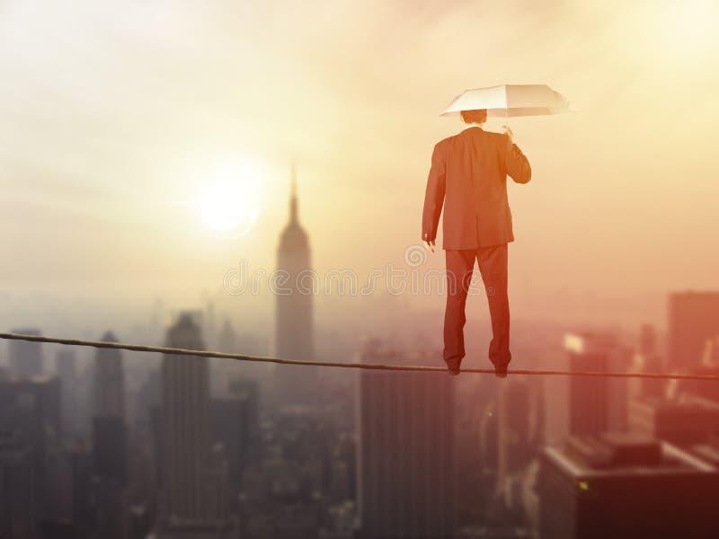 Arbeitsleben-Balancenkonzept: Geschäftsmann, der über der Stadt balanciert lizenzfreies stockbild
