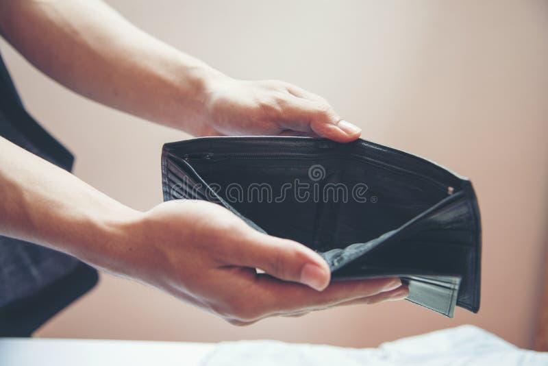 Arbeitsloser Mann, der leere Geldbörse zeigt Schließen Sie herauf Hände des offenen leeren Geldbeutels des armen Mannes stockfotografie