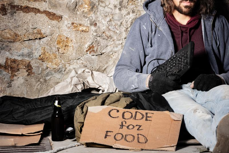 Arbeitsloser Mann sitzt mit Tastatur- und Pappzeichen lizenzfreie stockfotos