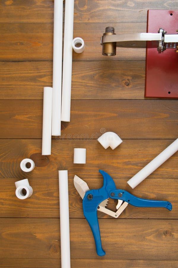 Arbeitsmoment im Bau der Hauptklempnerarbeit, der weißen Polypropylenrohre und der Werkzeuge des roten Lötkolbens lizenzfreie stockbilder