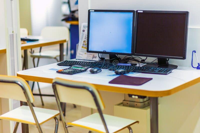 Arbeitsplätze bei einem Tisch mit zwei Computern in einem großen Einkaufszentrum stockbilder