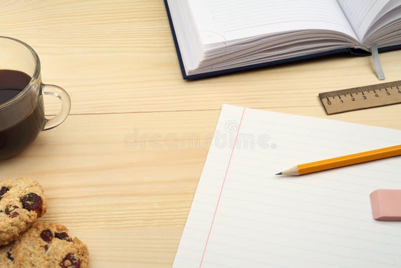 Arbeitsplatz, Büroartikel, Kaffeetasse und Plätzchen auf Holztisch lizenzfreie stockbilder