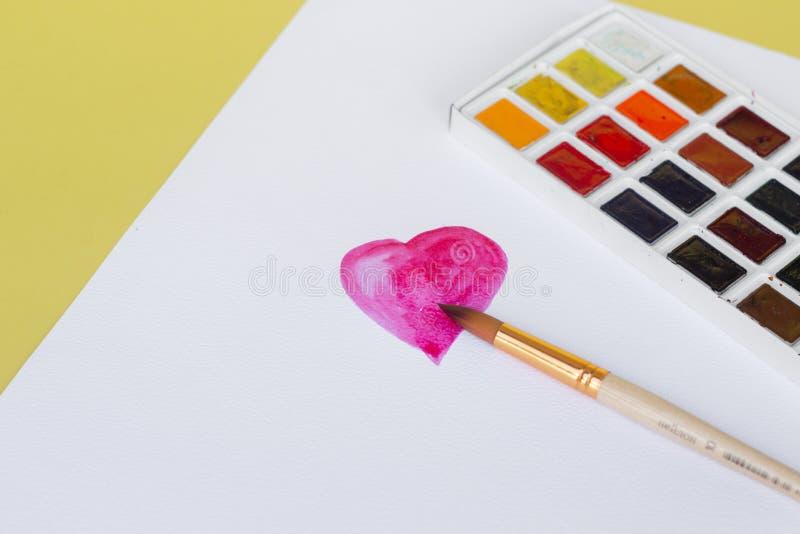 Arbeitsplatz des Künstlers mit Aquarellen und der Bürste im Innenministerium Herzform gezeichnet mit roten Aquarellen auf Weiß lizenzfreie stockfotos