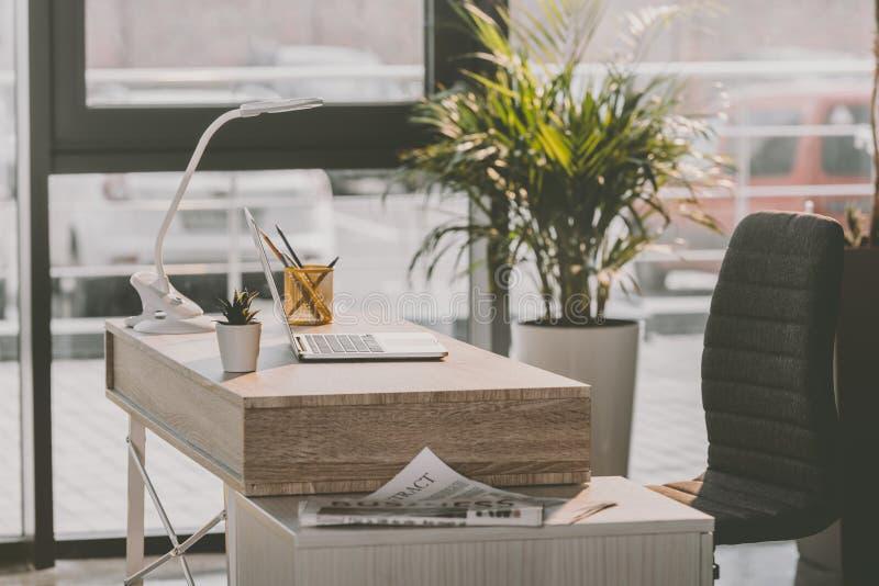 Arbeitsplatz mit Laptop-Computer und Zeitung im modernen Büro lizenzfreies stockfoto