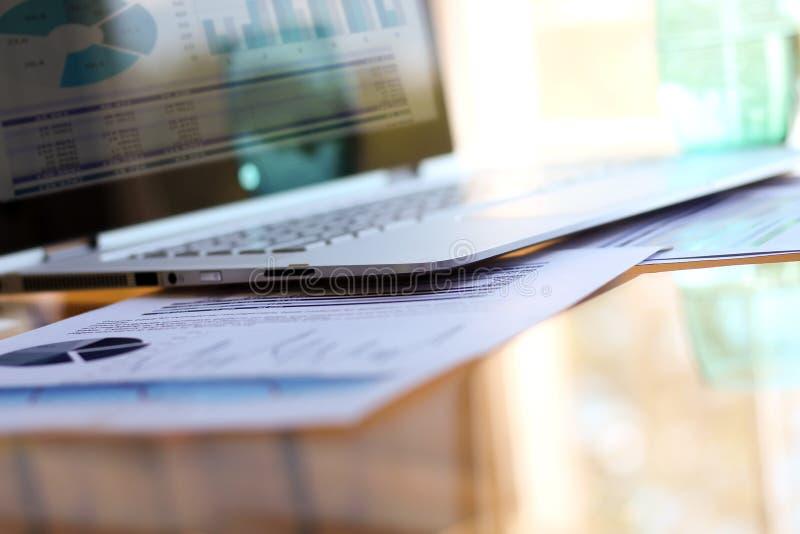Arbeitsplatz mit Laptop, digitale Tablette; Diagramme im Büro stockbilder
