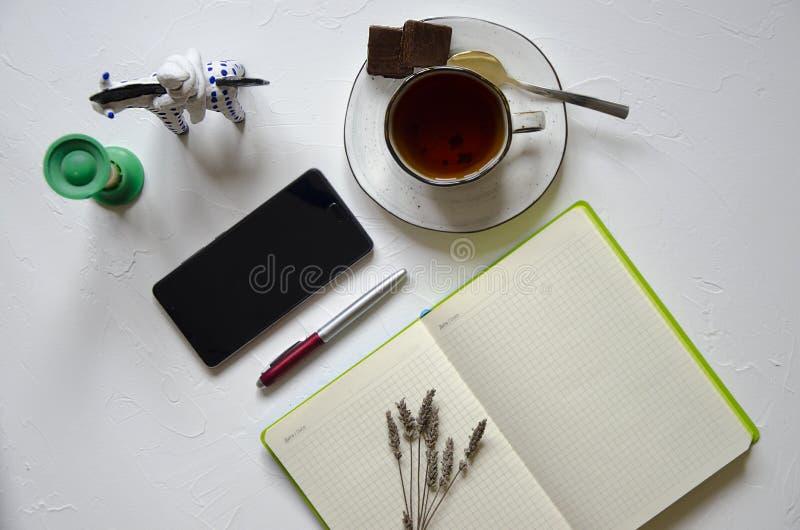Arbeitsplatz mit Notizblock, Tasse Tee auf einem wei?en Hintergrund Flache Lage, Draufsichtschreibtischschreibtisch Arbeitsplatzf lizenzfreie stockfotografie