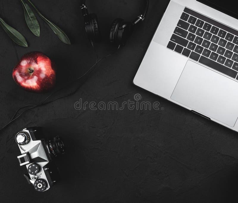 Arbeitsplatz mit offenem Laptop, eine Retro- Kamera und Zusatz auf Büro schwärzen Tabelle stockbild